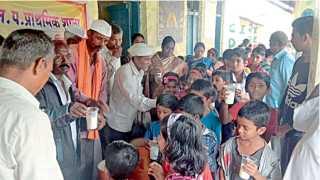 सोनगाव संमत निंब (ता. सातारा) - प्राथमिक शाळेतील मुलांना बुधवारी दूधवाटप करताना कमलाकर शिंदे व ग्रामस्थ.