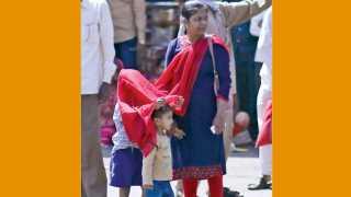 स्वारगेट - उन्हाच्या चटक्यापासून मुलांचे संरक्षण व्हावे, यासाठी त्यांच्या डोक्यावर ओढणी टाकून शेजारी उभी असलेली महिला.