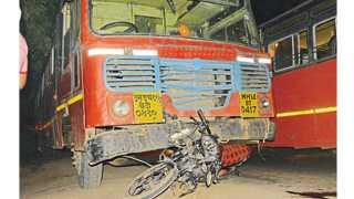 जळगाव - विद्युत कॉलनी थांब्याजवळील महामार्गावर मंगळवारी झालेल्या अपघातात बसखाली अडकलेली दुचाकी.