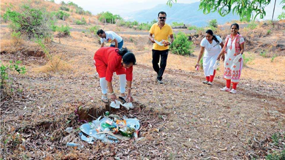 कासच्या मोकळ्या वातावरणात खानपान करून कचरा तेथेच टाकून जातात. तो कचरा गोळा करताना महिला.