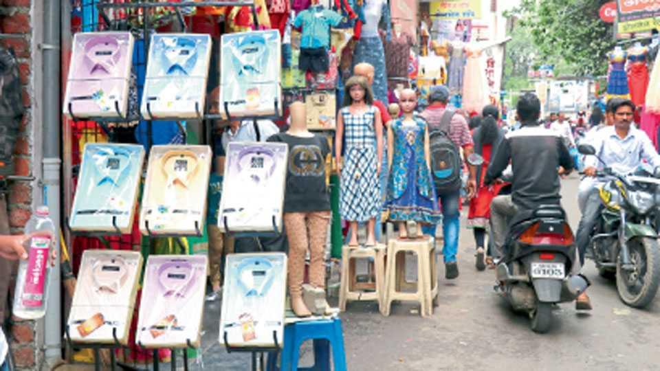 रस्त्यावर मांडलेले कपड्यांचे रॅक व जाहिरात करणारे पुतळे.