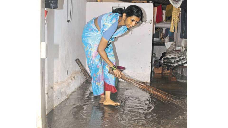 शास्त्रीनगर येथे पावसाचे पाणी घरात आल्याने पाणी बाहेर काढताना महिला.