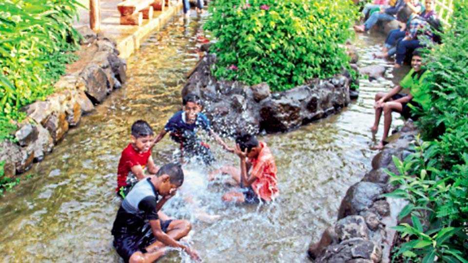 पाण्यात भिजण्याचा आनंद घेताना  मुले.
