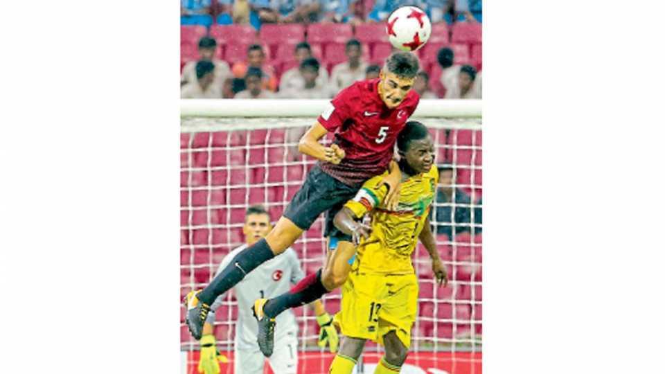 नवी मुंबई - मालीचा खेळाडू (लाल जर्सी) तुर्कस्तानच्या खेळाडूला चकवून (पिवळी जर्सी) हेडिंग करताना.
