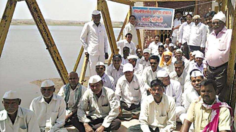 मालनगाव (ता. साक्री) - धरणावर पाणी बचावसाठी गुरुवारी आंदोलन करताना मालनगाव धरण बचाव संघर्ष समितीच्या सदस्यांसह शेतकरी.
