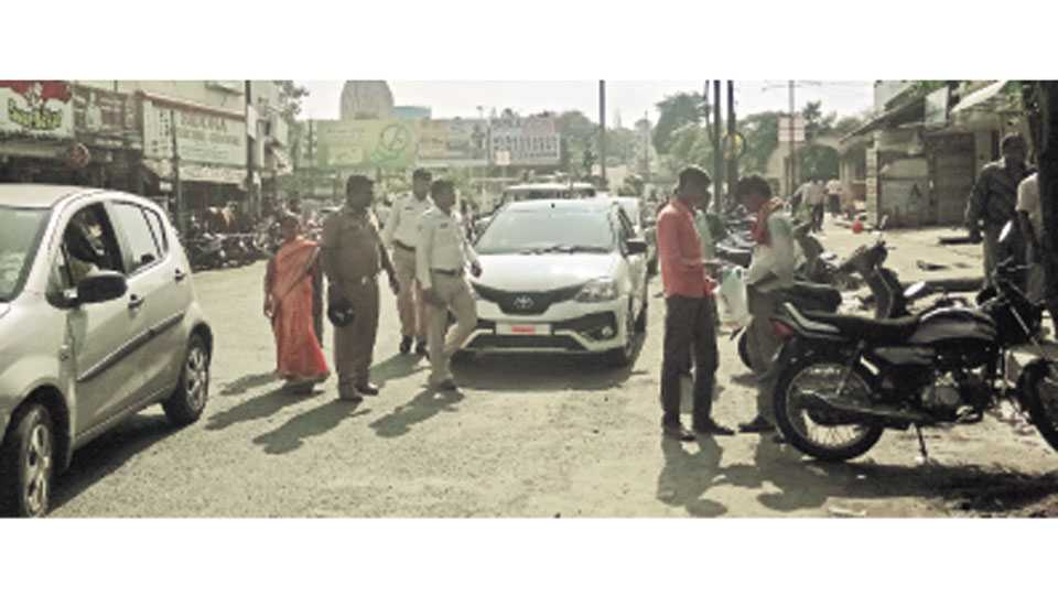 नागपूर - अयोग्य ठिकाणी कार पार्क करणाऱ्यांना समज देताना पोलिस.