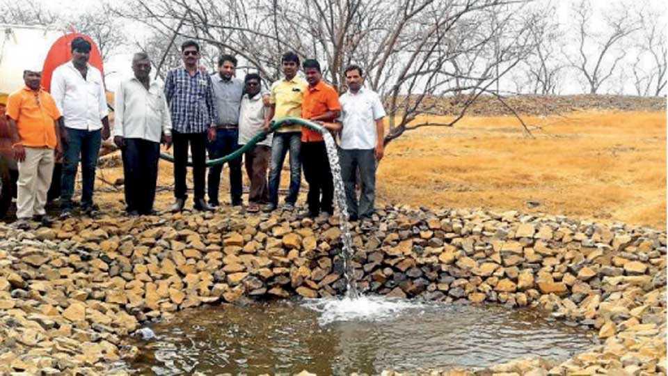 रोटी (ता. दौंड) - वनक्षेत्रातील नवीन झालेल्या पाणवठ्यात पाणी सोडताना माजी विद्यार्थी व वन अधिकारी.