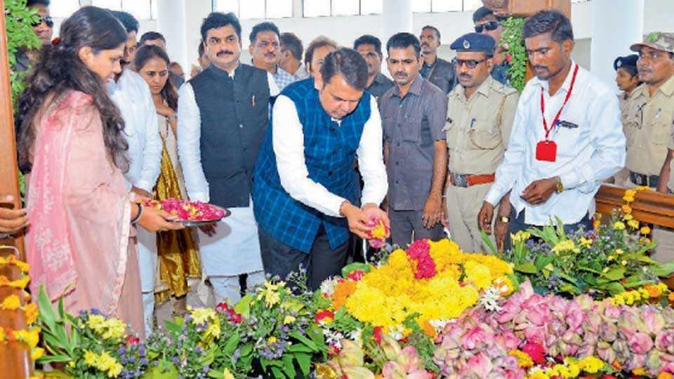 परळी - येथे माजी उपमुख्यमंत्री गोपीनाथ मुंडे यांच्या समाधिस्थळी पुष्प अर्पण करून अभिवादन करताना मुख्यमंत्री देवेंद्र फडणवीस. समवेत पंकजा मुंडे.