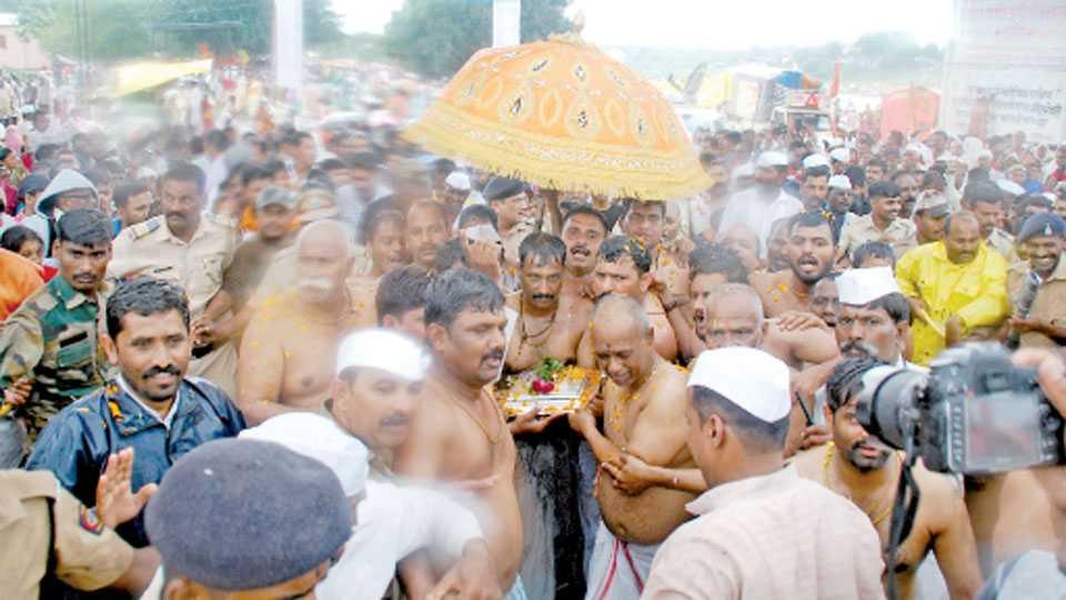 नीरा (ता. पुरंदर) - नीरास्नानासाठी शुक्रवारी माउलींच्या पादुकांना दत्त घाटावर घेऊन जाताना विश्वस्त व मानकरी.