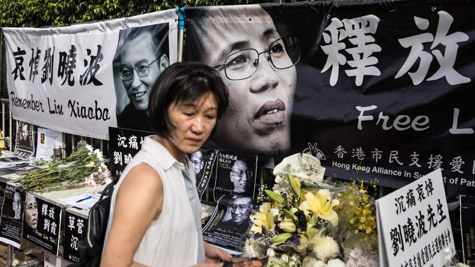A woman reacts as she visits a makeshift memorial for the late Chinese Nobel laureate Liu Xiaobo, outside the Chinese Liaison Office in Hong Kong