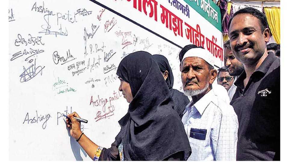सांगली - मुस्लिम आरक्षण आंदोलनाला पाठिंबा देण्यासाठी फलकावर स्वाक्षरी करताना मुस्लिम युवती. या वेळी उपस्थित मुस्लिम नागरिक.