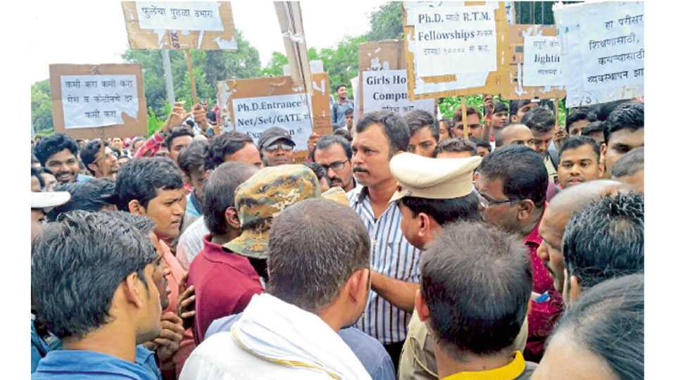 विद्यापीठ कॅम्पससमोर आंदोलनकर्त्या विद्यार्थ्यांशी चर्चा करून त्यांची समजूत काढताना पोलिस अधिकारी.