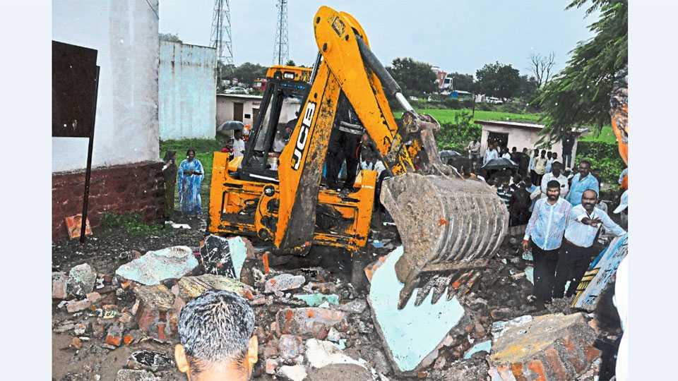 निंबोडी (ता. नगर) - यंत्राच्या साह्याने जिल्हा परिषद शाळेच्या इमारतीचा ढिगारा काढण्याचे सुरू असलेले काम.