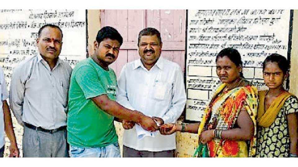 निमोणे (ता. शिरूर) - मायलेकींना आर्थिक मदत देताना स्थानिक तरुण.