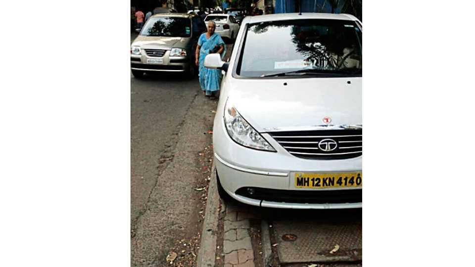 गरवारे चौक - पदपथावर वाहने उभी राहत असल्याने अडथळे पार करत चालत असलेल्या वृद्ध महिला.