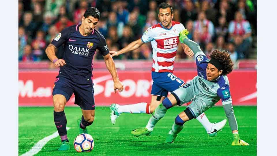 ग्रेनाडा - स्पॅनिश साखळी फुटबॉल स्पर्धेत बार्सिलोना संघाच्या लुईस सुआरेझला रोखण्याचा प्रयत्न करताना ग्रेनाडा संघाचा गोलरक्षक गुलेर्मो ओचा (उजवीकडेध आणि बचावपटू मॅथ्यू सौनिएर (मध्यभागी)