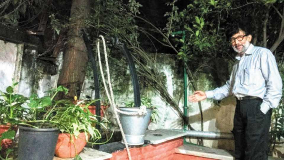 त्रिमूर्तीनगर - छतावरील पावसाचे पाणी विहिरीच्या बाजूने खोदलेल्या खड्ड्यात जिरवून 'रेन वॉटर हार्वेस्टिंग' करणारे डॉ. श्याम माधव धोंड.