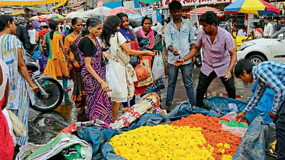 नऊ ऑगस्ट क्रांती दिन चौक - दसऱ्याकरिता पावसातही झेंडूच्या फुलांची खरेदी करताना नागरिक.