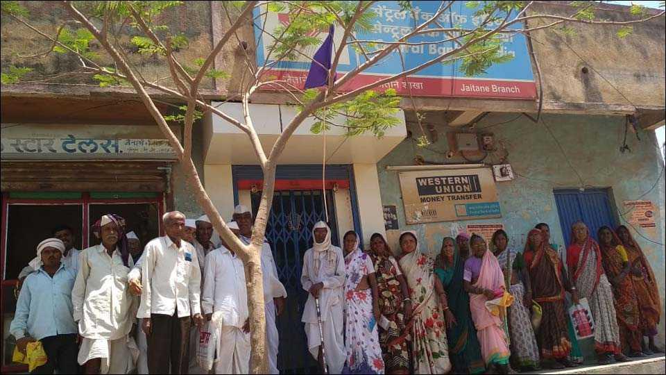 जैताणे (ता.साक्री) : तांत्रिक बिघाडामुळे सलग पाच दिवसांपासून सेंट्रल बँक शाखेचे कामकाज बंद पडल्याने कुलूपबंद बँक शाखेबाहेर ताटकळत उभे असलेले महिला व पुरुष ग्राहक. (छायाचित्र : प्रा. भगवान जगदाळे)