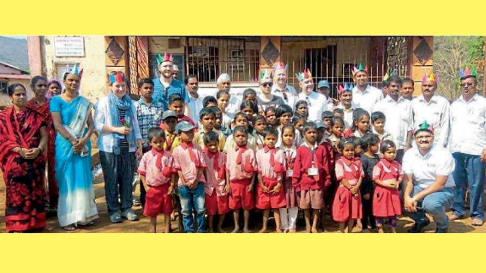पढारवाडी (ता. मुळशी) - शाळेतील मुलांसमवेत मुकुट परिधान केलेले परदेशी पाहुणे.
