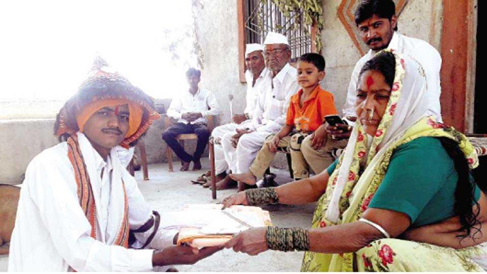 शेलगाव खुर्द (ता.फुलंब्री) - वासुदेवांना नवीन वस्त्रदान करताना महिला. (दुसऱ्या छायाचित्रात) मोराच्या पिसाऱ्यापासून तयार केलेला टोप.