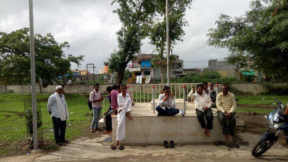 farmers protest sitting on the flag poll