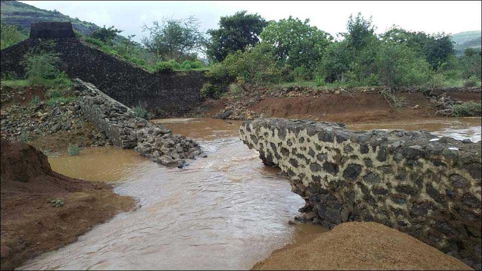 सांडवा तुटल्याने पाणी वाहून जात असताना.