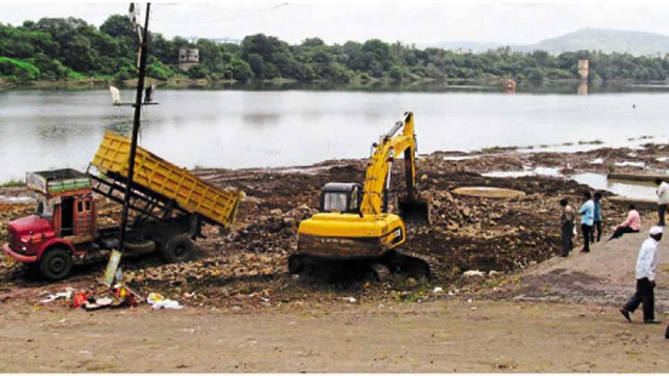 कऱ्हाड - कृष्णा घाटावर नदीपात्रात सोमवारी मुरूम टाकताना पालिकेचे कर्मचारी.