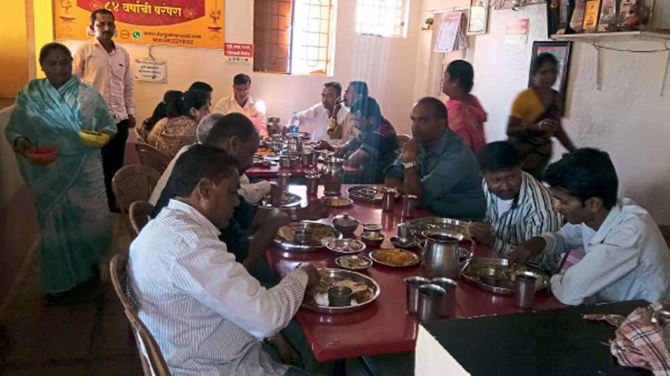 खानावळीत ग्राहकांना आपुलकीने जेवण वाढताना विमलताई जाधव