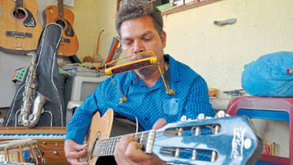 नाशिक - माउथ ऑर्गन आणि गिटार एकाच वेळी वादनाचा आनंद घेणारे संगीत शिक्षक हरीश उन्हवणे.