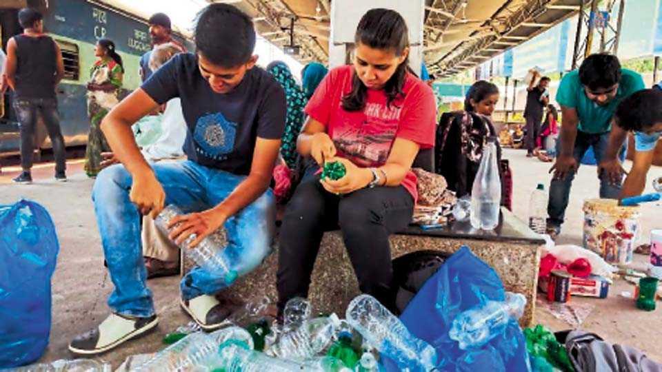 पुणे रेल्वेस्थानक - रोपांसाठी प्लास्टिकच्या बाटल्यांना आकार देताना तरुण.