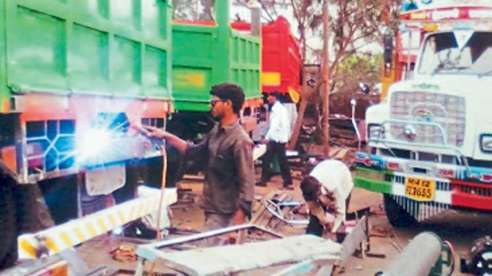 कात्रज (पुणे) - नवीन ट्रकची बॉडीनिर्मिती आणि रंगकाम करताना कारागिर.