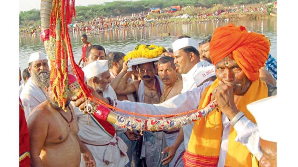 नीरा (ता. इंदापूर) - नीरास्नान आटोपल्यानंतर डोक्यावर पादुका घेऊन जाताना सोहळाप्रमुख.