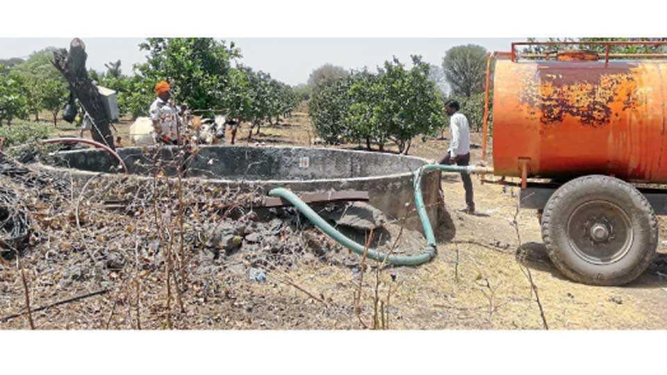 बुट्टेवाडगाव (ता. गंगापूर) - मोसंबी बागेसाठी टॅंकरद्वारे विहिरीत पाणी सोडताना शेतकरी.