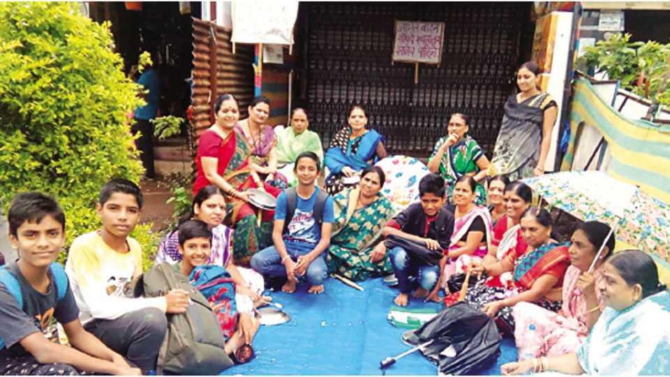 दिंडोरी रोड - दारू दुकानासमोर रविवारी ठिय्या आंदोलन करताना महिला व मुले.